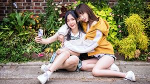 Asian Women Model Long Hair Dark Hair Sitting Sneakers Shorts Shirt Plants Bricks Wall Taking Selfie 2560x1706 Wallpaper