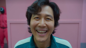 Netflix TV Series Korean Men Smile Pink Background Squid Game Lee Jung Jae Dark Hair Black Hair Asia 2600x1300 Wallpaper